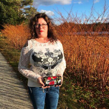 Bildet viser Laila Ramona som holder en Skulls And Roses lommebok fra RiffRaff.no Artikkelnummer: WBN1428