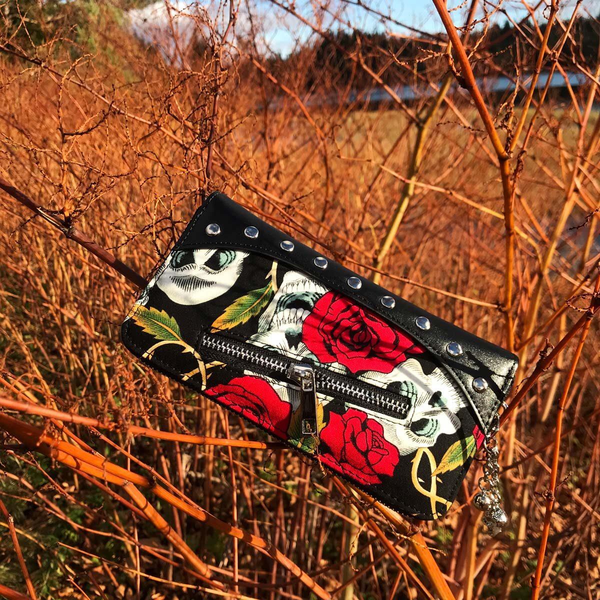 Bildet viser en Skulls And Roses lommebok fra RiffRaff.no hengende i en busk på vei til Vennesla. Artikkelnummer: WBN1428